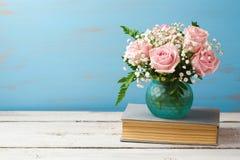 罗斯在花瓶的花花束在木背景的旧书 免版税库存照片