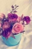 罗斯在蓝色杯子的束花在葡萄酒样式的装饰的 图库摄影