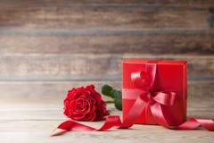 罗斯花和礼物盒在木土气桌上 母亲或情人节贺卡 复制文本的空间 库存照片