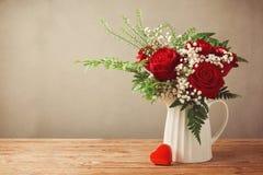 罗斯花花束和心脏塑造在木桌上的箱子与拷贝空间 免版税库存图片