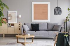 罗斯金绘画和海报在明亮的顶楼内部与灰色沙发在内阁和木桌附近 实际照片 免版税库存图片