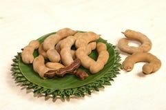 罗望子树在板材的果子服务由香蕉叶子装饰 图库摄影