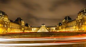 罗浮宫夜视图在巴黎,有汽车光的落后 免版税库存照片