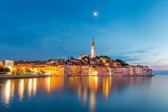 罗维尼镇,在Istrian半岛的西海岸的克罗地亚捕鱼港口五颜六色的日落  库存照片