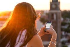 罗萨里奥,阿根廷- 2017年11月8日:日落的女孩与智能手机在她的手和一次whatsapp交谈上在屏幕上 免版税库存图片