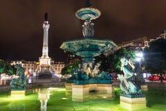 罗西乌广场,里斯本,有它的装饰喷泉之一的葡萄牙夜景和佩德罗的专栏IV 免版税图库摄影