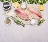 罗非鱼未加工的内圆角用香料和草本、柠檬和胡椒在一个切板在一张白色背景土气村庄顶视图 库存照片