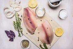 罗非鱼未加工的内圆角用香料和草本、柠檬和胡椒在一个切板在白色背景土气村庄顶视图 免版税库存照片