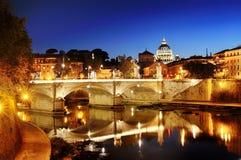 罗马、意大利-一座桥梁的看法在台伯河河的和圣皮特圣徒・彼得& x27; s大教堂圆顶在梵蒂冈在晚上 库存图片