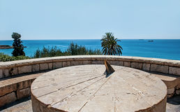 罗马在小山的日规葡萄酒大圆的石头在海上在水平晴朗的无云的天 免版税库存照片