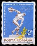 罗马尼亚、展示铁饼选手和奥林匹克圆环打印的邮票 库存照片