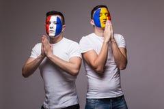 罗马尼亚和法国国家队的足球迷祈祷 足球迷概念 免版税图库摄影