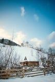 罗马尼亚小教会看法用雪盖的小山的 与东正教的冬天风景在蓝天和木篱芭 免版税库存照片
