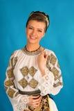 罗马尼亚民间传说给传统穿衣在蓝色azzure背景 库存照片