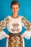 罗马尼亚民间传说给传统穿衣在蓝色azzure背景 免版税库存图片