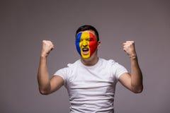 罗马尼亚足球迷的胜利,愉快和目标尖叫情感在罗马尼亚国家队比赛支持的在灰色背景的 库存图片
