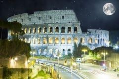 罗马斗兽场在晚上,罗马,有巨大的月亮的意大利 库存图片