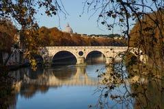 罗马,意大利-一座桥梁的风景看法在台伯河河的,背景圣伯多禄大教堂圆顶的 库存照片