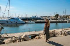 罗马,意大利- 2018年8月:年轻美女在口岸走在豪华游艇附近 免版税库存图片