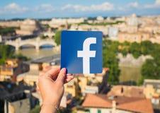 罗马,意大利- 2018年5月13日:对Facebook商标负的人手中与城市在背景中 免版税库存图片