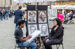 罗马,意大利- 2015年10月:一位有天才的街道艺术家画在妇女的纸画象的一支铅笔坐椅子在来源附近 免版税库存照片