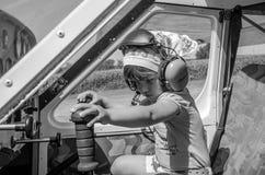 罗马,意大利- 2017年7月:小迷人的小女孩飞行员,孩子在轻引擎航空器Tecnam P92-S回声驾驶舱内  库存照片