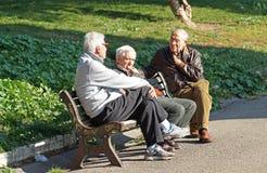 罗马,意大利- 2015年11月20日:交谈 三个老人交谈的坐一条长凳在公园晴天  免版税库存照片