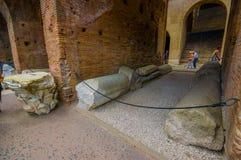罗马,意大利- 2015年6月13日:在巨大的曲拱之间的大石头在罗马大剧场,参观这座纪念碑的人们里面 库存照片