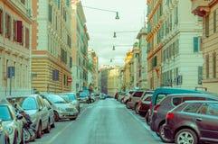 罗马,意大利- 2015年6月13日:长的典型的街道在有汽车的罗马在边,与街道照明的好的看法 免版税库存图片