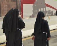 罗马,意大利10月07日2018年,在黑长袍打扮的三位尼姑走罗马,从后面的看法街道  库存图片