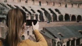 罗马,意大利11 02 2017站立在罗马斗兽场里面和拍在智能手机的少妇照片,享受看法 股票录像