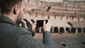 罗马,意大利11 02 2017站立里面罗马斗兽场和拍在智能手机的年轻英俊的人照片,享受看法 股票视频