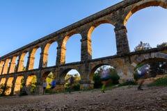 罗马Aqueduct Pont del Diable美丽的景色在日落的塔拉贡纳与跑步在它前面的人 图库摄影