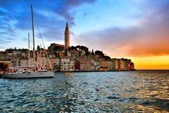 罗维尼,有充满活力的日落的克罗地亚海边老镇  库存照片