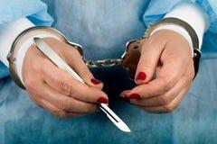 罪犯在手中把有柳叶刀解剖刀的医疗人扣上手铐 免版税库存照片