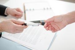 给署名的商人一支笔 免版税库存照片