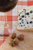 羊乳干酪乳酪用橄榄和一杯红葡萄酒 免版税库存图片