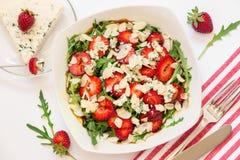 羊乳干酪草莓芝麻菜沙拉和利器在餐巾 免版税库存图片