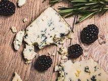 羊乳干酪,与模子的法国蓝色乳酪在一张木桌上,服务用黑莓和迷迭香,欢乐和健康小树枝  免版税库存照片