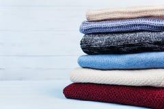 羊毛毛线衣和被编织的冬天堆在蓝色木背景穿衣 复制文本的空间 图库摄影