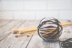 羊毛现代颜色球减速火箭的照片与编织的竹针的 定调子 库存图片