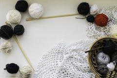 羊毛球、两根编织针、羊毛球在黏土碗和钩针编织的餐巾在中立背景 平的位置 空间为 免版税图库摄影