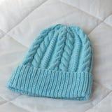 从羊毛用手编织的蓝色帽子 免版税库存图片
