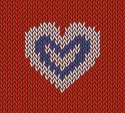 羊毛编织了与白色心脏的样式在红色背景 库存照片