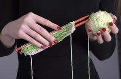 羊毛编织针和球在妇女` s手上 免版税库存图片