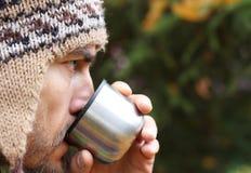 羊毛被编织的帽子的有胡子的人从杯子,在外形的面孔喝 免版税库存照片