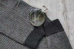 羊毛运动衫,一个瓶香水 库存图片