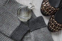 羊毛运动衫,妇女` s鞋子和一个瓶香水 免版税库存照片