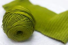 羊毛绿色丝球与一个被编织的部分的 免版税库存图片