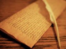 羊皮纸和羽毛纤管写的在木书桌 免版税图库摄影